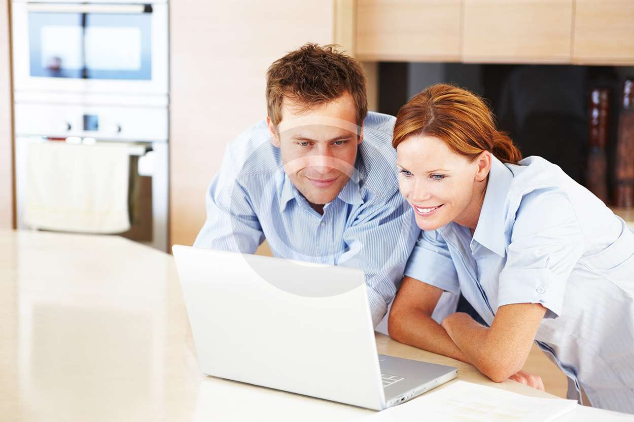 Portrait of a cute young couple looking at the laptop screen